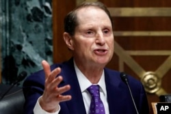 FILE - Sen. Ron Wyden, D-Ore., asks a question during a Senate Finance Committee meeting on Capitol Hill, June 20, 2018, in Washington.