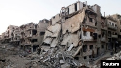 A general view shows damaged buildings on a deserted street in the besieged area of Homs, Syria, July 12, 2013.