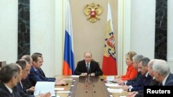 "Russian President Vladimir Putin (C) chairs a meeting with members of the Security Council at the Kremlin in Moscow, Mar. 6, 2015. Russia is seen as using propaganda and money to, as one analyst put it, ""divide and split Europe."""