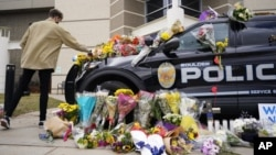 In this March 23, 2021, photo, a man leaves a bouquet on a police cruiser parked outside the Boulder Police Department after an officer was one of the victims of a mass shooting at a King Soopers grocery store in Boulder, Colorado. (AP)