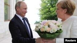 Russian President Vladimir Putin welcomes German Chancellor Angela Merkel during their meeting in the Black Sea resort of Sochi, Russia, May 18, 2018.