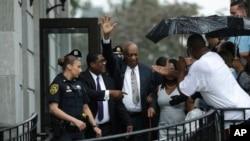 Bill Cosby (giữa) giơ tay chào trong khi rời khỏi Tòa án Quận Montgomery với người đặc trách quan hệ công chúng Andrew Wyatt của ông sau khi thẩm phát tuyên bố xét xử vô hiệu ở Norristown, Pennsylvania, ngày 17 tháng 6, 2017.