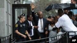 Bill Cosby, tengah, melambaikan tangan saat keluar dari Gedung Pengadilan Montgomery County, bersama agennya Andrew Wyatt, kedua dari kiri setelah batal sidang dinyatakan dalam pengadilan penyerangan seksual di Norristown, Pa, Sabtu, 17 Juni 2017 (foto: AP Photo/Matt Slocum)