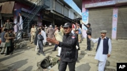 Policemen ask residents to disperse as they stand near the site of a deadly suicide bomb attack at a paramilitary training center in Mardan, northwest Pakistan, February 10, 2011.