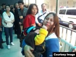 王登朝的妻子怀抱幼子与围观者在法院外。(网络图片)