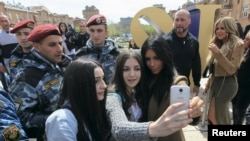 U.S. television personality Kim Kardashian (R, front) poses for a picture with local residents, with her sister Khloe Kardashian standing nearby, while sightseeing in central Yerevan, April 9, 2015.