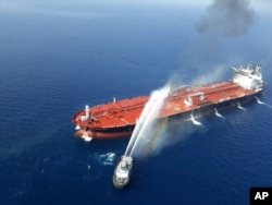 An Iranian navy boat sprays water to extinguish a fire on an oil tanker in the sea of Oman, June 13, 2019.