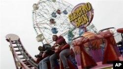 "Dua pengunjung Coney Island sedang menaiki wahana ""Electro Spin"" di Luna Park (foto: Dok)."