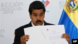 Nicolas Maduro holds official certificate declaring him winner of presidential election, Electoral Council, Caracas, April 15, 2013.