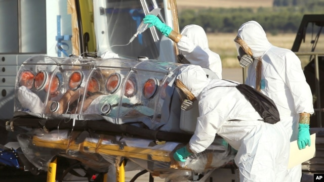 In this photo provided by the Spanish Defense Ministry, aid workers and doctors transfer Miguel Pajares, a Spanish priest who was infected with the Ebola virus while working in Liberia, from a plane to an ambulance as he leaves the Torrejon de Ardoz milit
