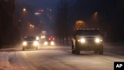 Drivers slowly make their way down a normally busy road during a snowy rush hour in Charlotte, North Carolina, Jan. 28, 2014.