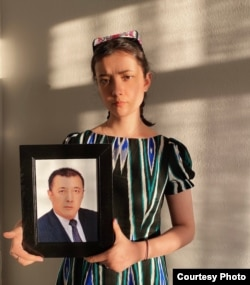 Aykanat Wahitjan holds a picture of her father, Wahitjan Osman, in Istanbul in April. (Photo courtesy of Aykanat Wahitjan)