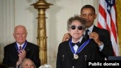 """지난 2012년 바락 오바마 미국 대통령으로부터 민간인 최고 상훈 가운데 하나인 '자유의 메달'을 수여받고 있는 가수 밥 딜런(앞). 오바마 대통령은 """"딜런은 음악을 통해 사람들에게 메시지를 전했고, 미국 대중음악 역사에서 딜런 같은 거인은 없었다""""고 말했다."""