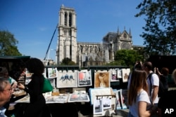 People walk near Notre Dame in Paris, April 19, 2019. The 800-year-old cathedral was devastated by fire this week.