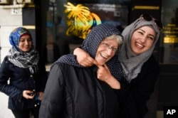 Syrian refugee Nada Alshebli, right, jokingly places a 'hijab' veil on Uruguayan Sonia de Leon as her sister Fatima walks behind them on a stroll through Juan Lacaze, Uruguay.
