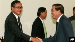 Cambodian Prime Minister Hun Sen shakes hands with opposition leader Sam Rainsy before a meeting at the National Assembly.