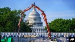 FILE - A concrete pump frames the Capitol Dome during renovations and repairs to Lower Senate Park on Capitol Hill in Washington, May 18, 2021. Senators on Wednesday reached rare bipartisan preliminary agreement on a massive infrastructure bill.