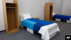Two sets of bedroom furniture, including cardboard beds, for the Tokyo 2020 Olympic and Paralympic Villages are shown in a display room Thursday, Jan. 9, 2020, in Tokyo. (AP Photo/Jae C. Hong)