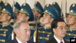 Chinese President Hu Jintao (R) and his Kazakh counterpart Nursultan Nazarbayev inspect the honor guard during an official welcoming ceremony in Astana, June 13, 2011.