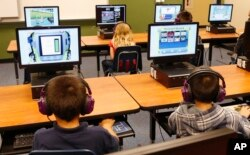 FILE - Students at a summer reading academy at Buchanan elementary school work in the computer lab in Oklahoma City.