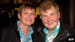 New Zealand entertainer Lynda Top (R) and her partner Donna Top join gay-rights supporters as they wait outside the parliament building in Wellington on April 17, 2013 for a place in the public gallery to see the chamber vote on a bill amending the 1955 M
