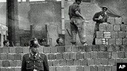 1961年10月7日,一名西柏林卫兵站在分隔东西柏林的混凝土墙前,同时,东德工人在为这道墙添砖加高。(资料照片)