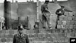 A West Berlin guard stands in front of the concrete wall dividing East and West Berlin at Bernauer Strasse, as East Berlin workmen add blocks to the wall to increase the height of the barrier, October 7, 1961 (file photo)