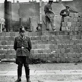 Một cảnh vệ Tây Berlin đứng trước bức tường bê tông chia cắt Đông và Tây Berlin ở Bernauer Strasse, trong khi các công nhân Đông Berlin chất các khối gạch lên bức tường để xây cao bức tường chắn này, 7/10/1961.