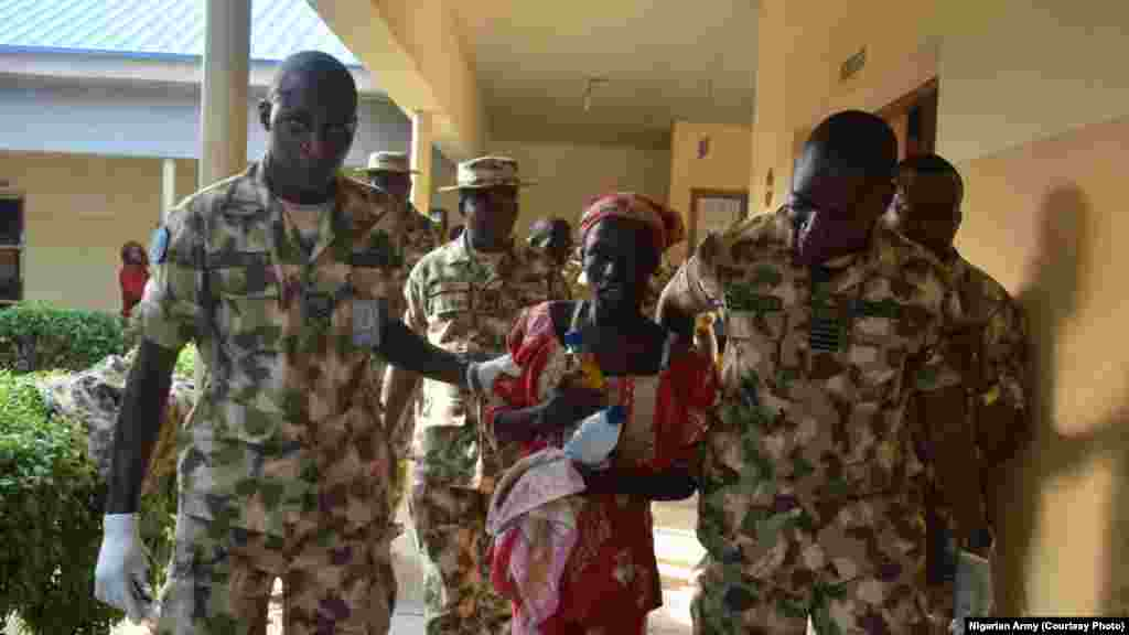 Amina Ali is escorted by Nigerian military personnel after being airlifted to Maiduguri.