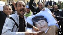 Masu zanga zanga suke lalata hoton shugaba Gadhafi a Zawiya,ranar lahadi.