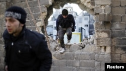 Free Syria Army fighters move through a hole in a wall during a fight with forces loyal to President Bashar al Assad at the front line in Aleppo December 24, 2012.