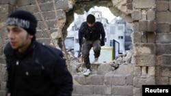 敘利亞反對派戰鬥人員12月24日在阿勒頗與政府軍戰鬥期間穿越一個洞穴。