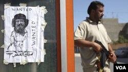 Tentara pemberontak berdiri di dekat poster 'Wanted: Moammar Gadhafi' di ibukota Tripoli, Libya (30/8).