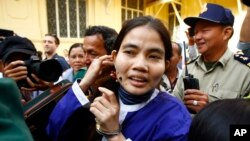 Yorm Bopha, right, a Boeung Kak lake villager, enters a court room for her hearing at the Supreme Court in Phnom Penh, Cambodia, Friday, Nov. 22, 2013.