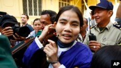 Yorm Bopha, right, a Boeung Kak lake villager, enters a court room for her hearing at the Supreme Court in Phnom Penh, Cambodia, Friday, Nov. 22, 2013. Cambodia's highest court released Bopha on bail Friday after she served more than a year in prison on charges widely condemned as trumped up to silence a government critic. The Supreme Court sent Yorm Bopha's case back to the Appeals Court for further investigation and a possible retrial. (AP Photo/Heng Sinith)