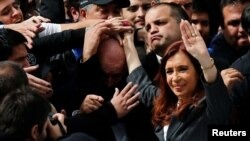 Former Argentine President Cristina Fernandez de Kirchner waves to supporters as she leaves a Justice building where she attended court to answer questions over a probe into the sale of U.S. dollar futures contracts at below-market rates by the central bank during her administration, in Buenos Aires, April 13, 2016.