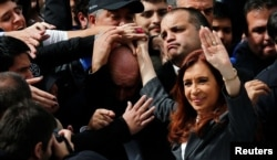 Former Argentine President Cristina Fernandez de Kirchner waves to supporters as she leaves a Justice building where she attended court to answer questions over a probe into the sale of U.S. dollar futures contracts at below-market rates by the central bank.