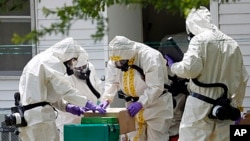 FILE - Federal agents wearing hazardous material suits and breathing apparatus inspect the home and possessions in the West Hills Subdivision house of Paul Kevin Curtis in Corinth, Miss., April 19, 2013.