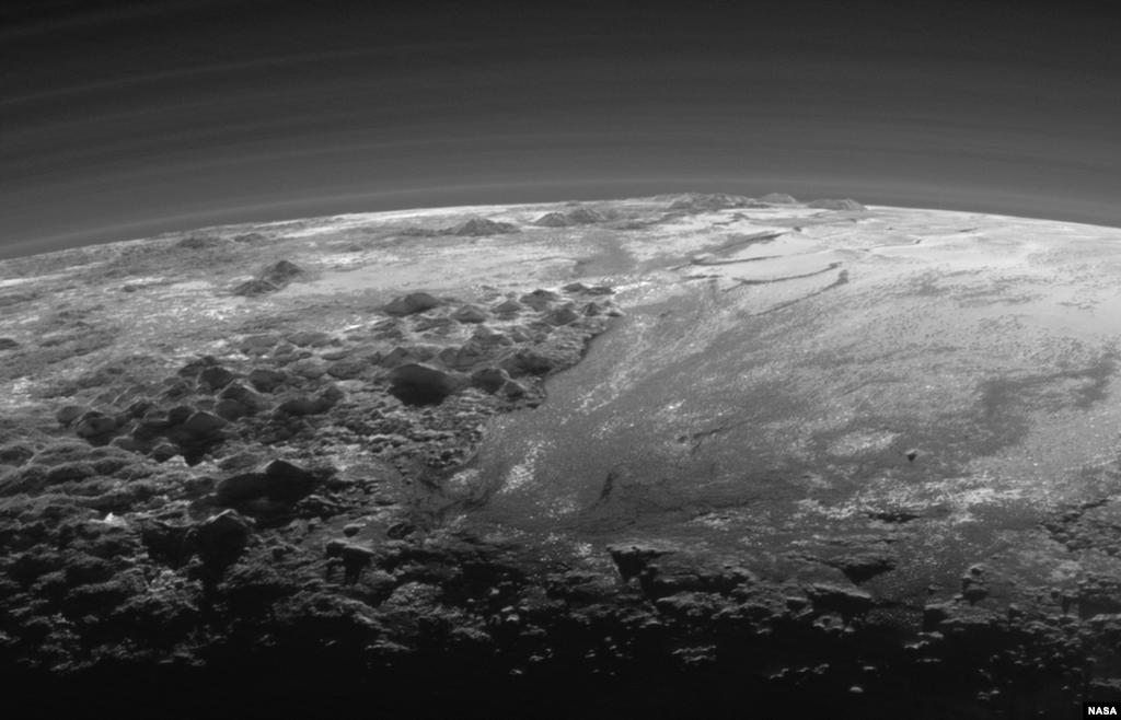 យានអវកាស New Horizons របស់អង្គការ NASA ចាប់យកទស្សនីយភាពជិតពេលព្រះអាទិត្យលិចនៅតំបន់ភ្នំប្រកបដោយទឹកកកមួយ និងវាលទំនាបទឹកកកលាតសន្ធឹងទៅជ្រោយសន្លឹមនៃភព Pluto។