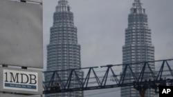 ສັນຍາລັກຂອງບໍລິສັດ 1MDB (1 Malaysia Development Berhad) ເຫັນຢູ່ຕິດກັບຕຶກແຝດ Petronas ນະຄອນຫຼວງ ກົວລາລຳເປີ, ມາເລເຊຍ.