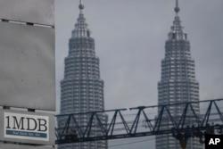 ປ້າຍ 1MDB (1 Malaysia Development Berhad) ຕິດຢູ່ຕໍ່ໜ້າ Petronas ຕຶກແຝດ ທີ່ນະຄອນ Kuala Lumpur ປະເທດ Malaysia.
