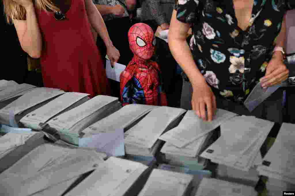 A kid in a Spiderman costume stands next to a ballot table for the European Parliament election at a polling station in Madrid, Spain.