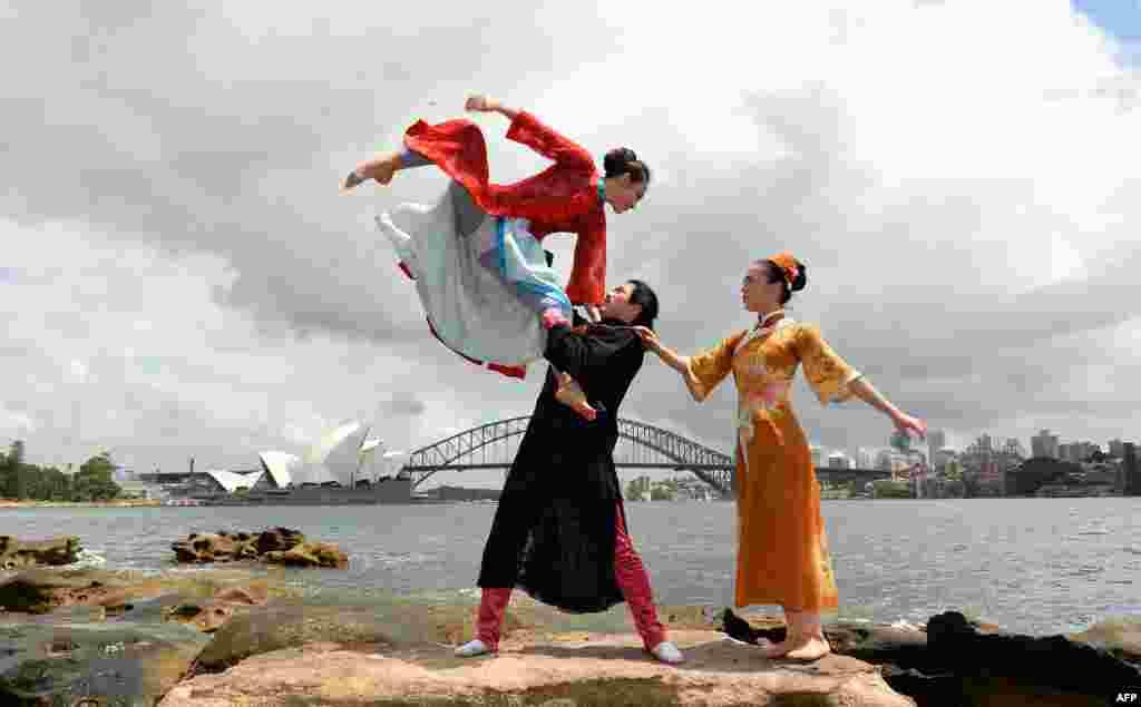 Elementos de uma companhia de ballet chinesa numa sessão fotográfica na Austrália, com Opera House e ponte de Harbour ao fundo, em Sidney. Zhang Yashu (topo), Tang Chenglong e Xia (E-D).