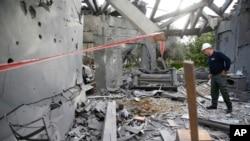 یک افسر پلیس اسرائیل در حال بررسی خانه ای که در اثر پرتاب یک راکت در مرکز اسرائیل، آسیب دید - دوشنبه ۵ فروردین