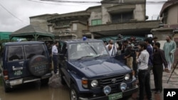 Pakistani media follow a senior police officer at outside the house of a abducted American citizen in Lahore, Pakistan, August 13, 2011