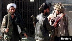FILE - Islamic Taliban militia, trying to enforce a rigid interpretation of Shariah law, use a whip to force locals to attend the Friday prayer at the Pole-Kheshti mosque in central Kabul, Nov. 8, 1996.