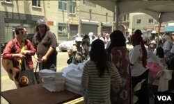 Skid Row residents go through the line, bagging basic necessities such as clothing, towels and soap.