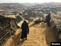 FILE - A woman walks up a hill in the Kutupalong camp for Rohingya refugees in southern Bangladesh, Feb. 11, 2018.