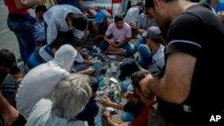ARHIVA - Migranti pune mobilne telefone u blizini Horgoša