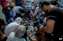 FILE - Migrants charge their mobile phones at the border station between Serbia and Hungary near Horgos, Serbia, Wednesday, Sept. 16, 2015.